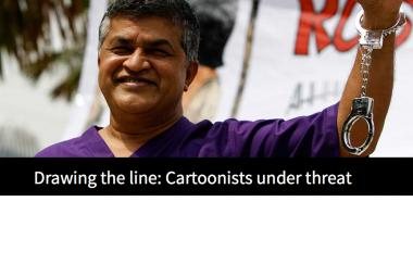 The Malaysian cartoonist Zunar raises a handcuffed arm at an event to promote his book in February 2015. Zunar is facing nine sedition charges. (AP/Joshua Paul)